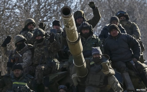 Ukrainian servicemen ride on a military vehicle as they leave area around Debaltseve, eastern Ukraine near Artemivsk, 18 February 2015