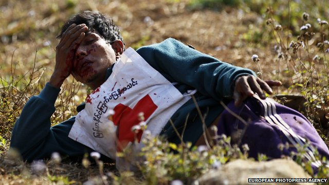 A wounded Red Cross volunteer lies on ground after vehicles of a rescue convoy were attacked in the Kokang region on 17 February 2015