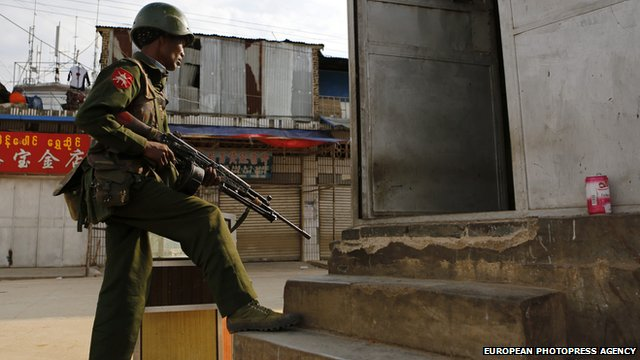 Armed military soldier takes position at the corner of a street in Laukkai, Myanmar on 16 February 2015