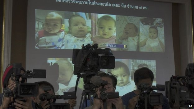 In this Aug. 12, 2014 file photo, the media cover as Thai police display pictures of surrogate babies born to a Japanese man who is at the center of a surrogacy scandal during a press conference at the police headquarters in Chonburi, Thailand