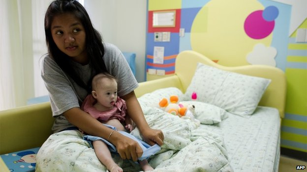 Thai surrogate mother Pattaramon Chanbua (L) holds her baby Gammy, born with Down's Syndrome, at the Samitivej hospital, Sriracha district in Chonburi province on August 4, 2014