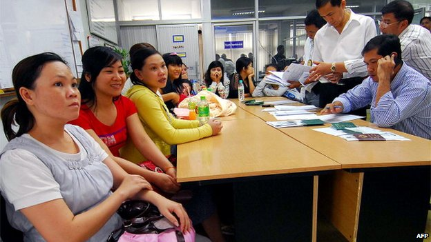 Thai immigration policemen (R) investigate Vietnamese women who were allegedly lured into becoming surrogate mothers at Immigration Police Bureau in Bangkok on February 24, 2011