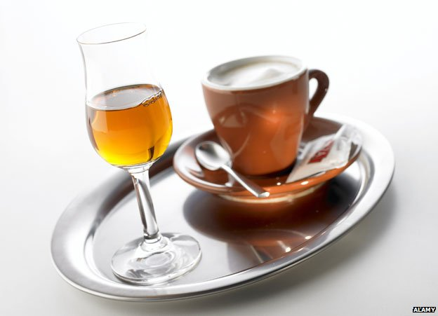 grappa glass with coffee in cup