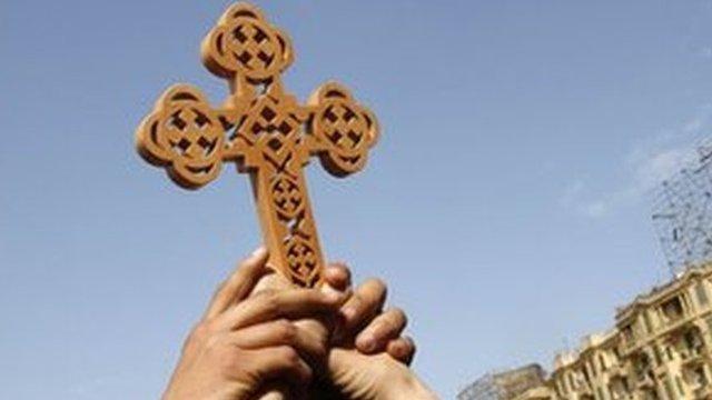Egyptian Coptic Christians hold a cross