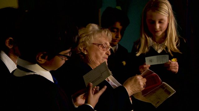 Children look at old ration books with Gladys
