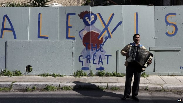A busker plays in front of a sign supporting Greek PM Alexis Tsipras (21 Feb)