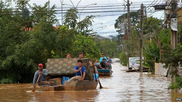 Affected residents try to save some furniture after heavy rain led to flooding in Cobija on 24 February 2015