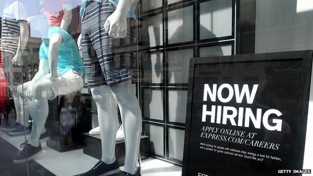 Shop window with 'Now hiring' sign