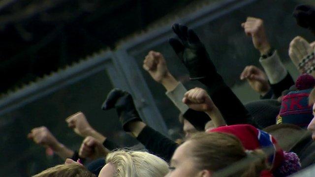 football fans raise their firsts
