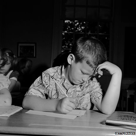 An American schoolboy puzzling over a maths test in 1955