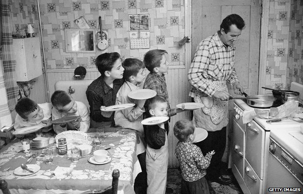 Seven siblings queuing for dinner, around 1955