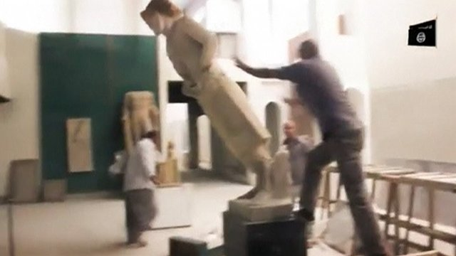 A man pushes a statue off its plinth in a museum at a location said to be Mosul in this still image taken from an undated video