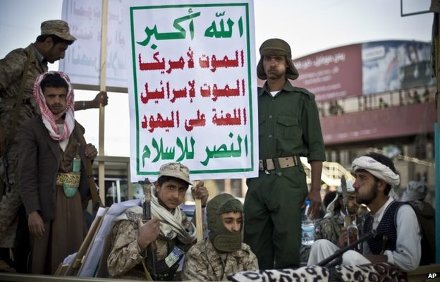 """Armed Houthi rebels in Sanaa carry a poster saying: """"God is great. Death to America. Death to Israel. A curse on the Jews. Victory to Islam."""" (23 January 2015)"""