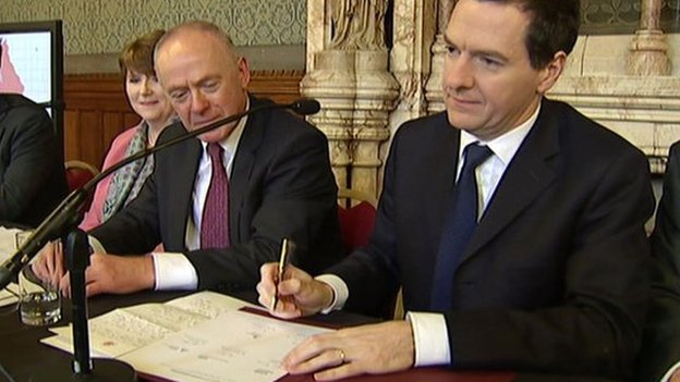 Chancellor George Osborne (right) signing the devolution agreement. He is sat next Sir Richard Leese, deputy leader of Greater Manchester Combined Authority