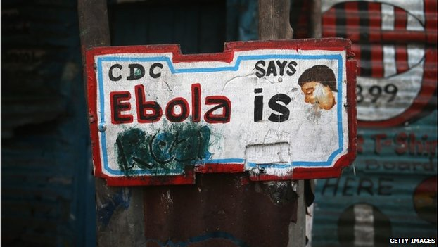 "A sign, originally saying ""Ebola is Real,"" hangs defaced in the West Point township in Monrovia"