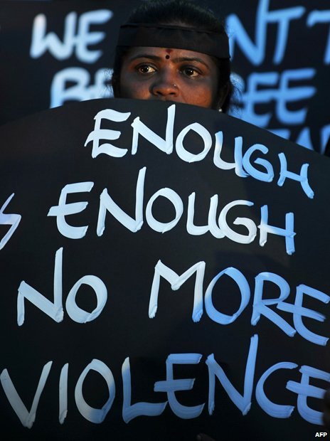 "A sign reading ""Enough is enough, no more violence"""