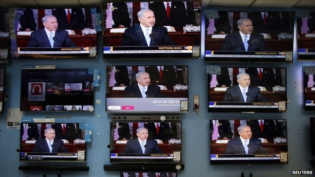 Israel's Prime Minister Benjamin Netanyahu is seen delivering his speech to the U.S. Congress on television screens in an electronics store in a Jerusalem shopping mall 3 March 2015