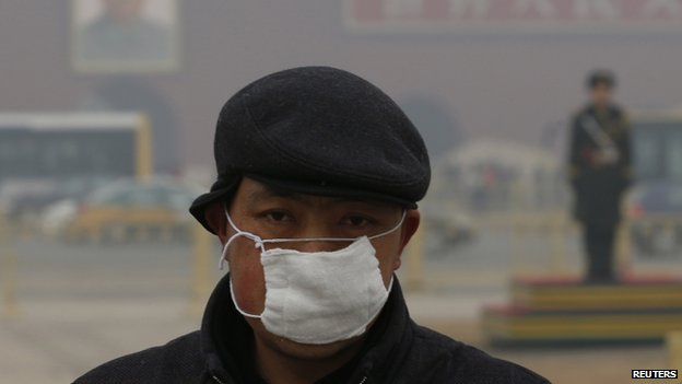 A man wears a mask as he makes his way during a polluted day at Tiananmen Square in Beijing 15 January 2015