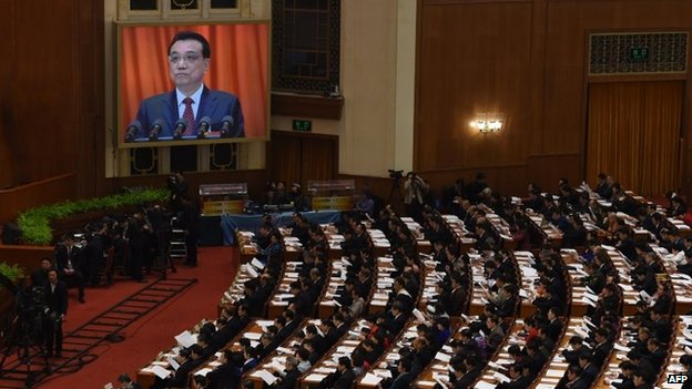 Delegates listen to Chinese premier Li Keqiang (on the screen) as he delivers his work report during the opening of the third session of the 12th National People's Congress at the Great Hall of the People in Beijing on March 5, 2015