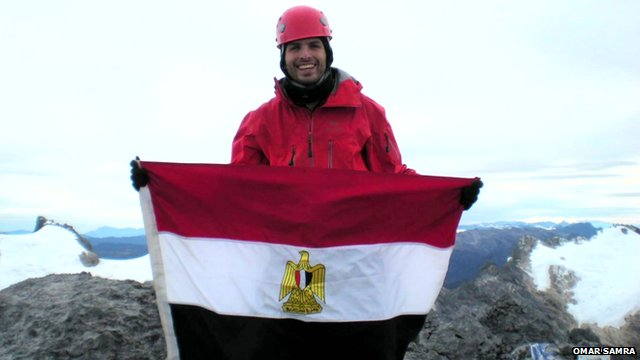 Omar Samra at the pinnacle of a mountain with a flag