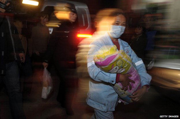 December 18, 2012 shows a medic (C) holding a rescued baby in her hands in Xichang, southwest China's Sichuan province