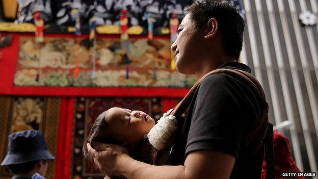 A Japanese father holding his sleeping baby