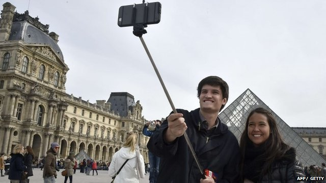 Tourists use a selfie-stick to take a picture of themselves outside the Louvre in Paris