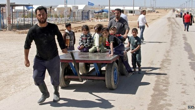 A Syrian refugee pulls a cart carrying children at the Zattari refugee camp near Mafraq city, Jordan - 14 March 2015