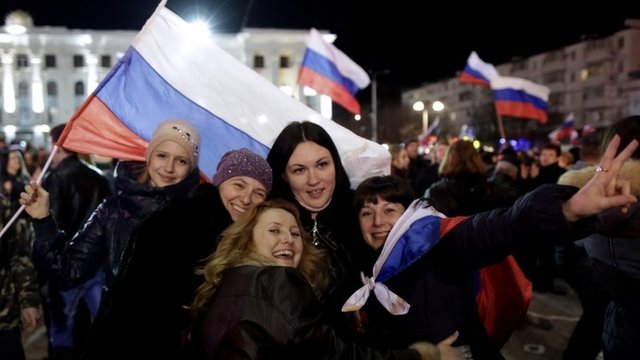 Women pose for a picture during a concert marking the one-year anniversary of Crimea voting to leave Ukraine and join the Russian state, in central Simferopol