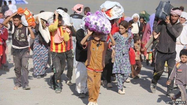 Displaced Iraqi families from the Yazidi community cross the Iraqi-Syrian border at the Fishkhabur crossing, in northern Iraq, on August 13, 2014.