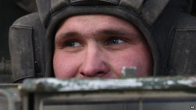 Close up of Ukrainian soldier's face as he looks over top of military vehicle