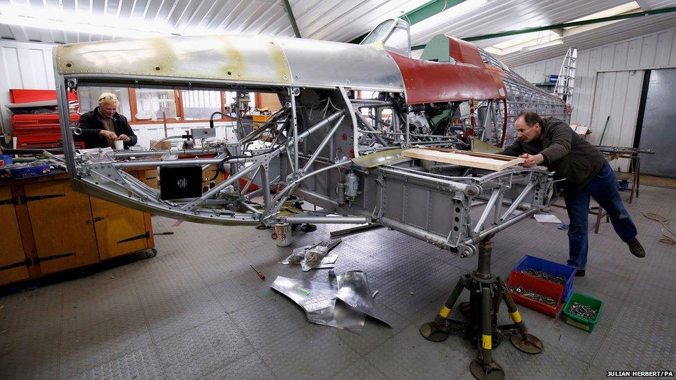 Engineers from Hawker Restorations Ltd work on a Hawker Hurricane Mk 1 in their Suffolk workshop