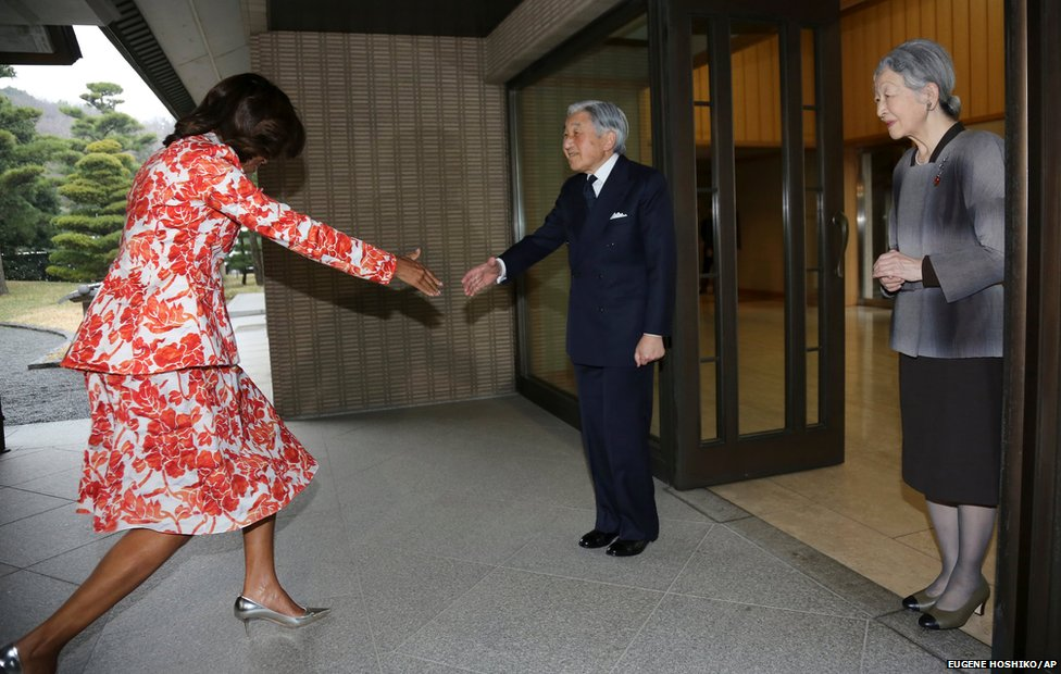 US first lady Michelle Obama (left) recovers from a stumble before shaking hands with Emperor Akihito