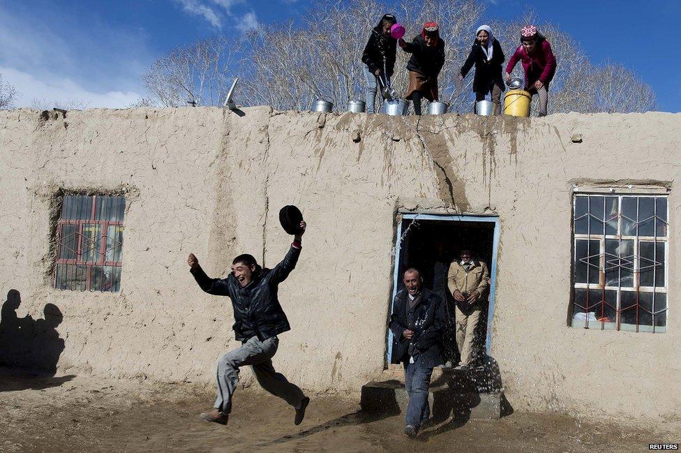 Tadjik women throw water on men from a roof top