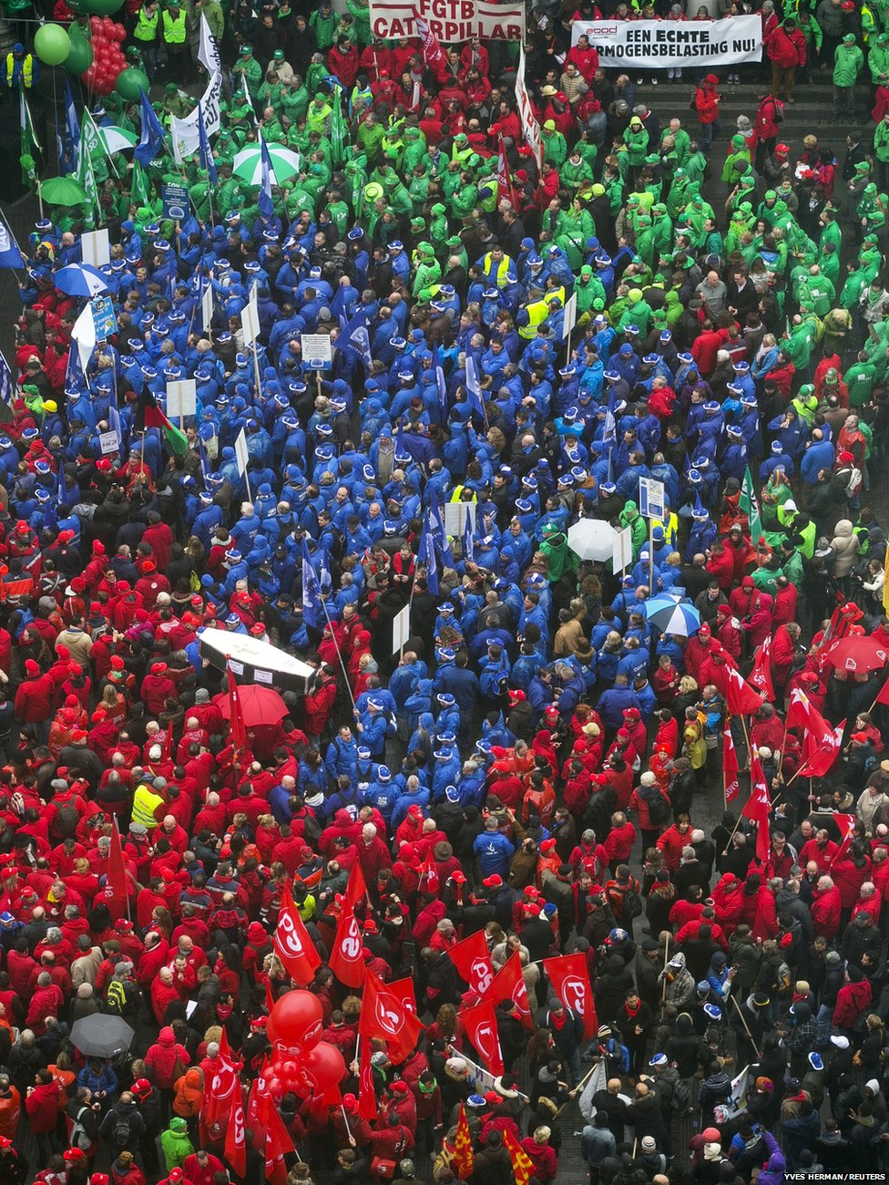Protesters wearing red (Socialists), blue (Liberals) and green (Christian Democrats) vests gather in central Brussels during a trade union meeting