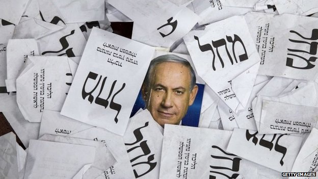 Copies of ballots papers and campaign posters for Israel's Prime Minister Benjamin Netanyahu's Likud Party lie on the ground in the aftermath of the country's parliamentary elections, early on 18 March