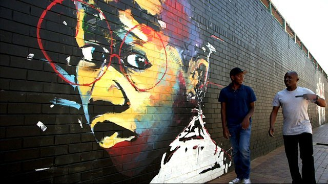 Graffiti on a wall as DJ edu walks past with an entrepreneur