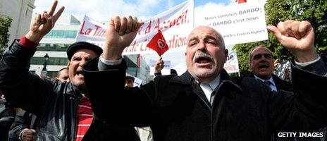Tunisian tourist guides shout slogans as they wave banners and their national flag during a demonstration on Bourguiba Avenue in Tunis on 20 March