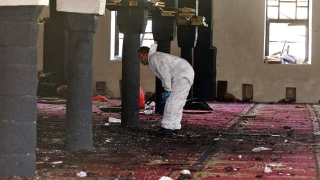 A forensic expert inspects the scene of a suicide attack targeting the al-Hashahush mosque in Sana'a