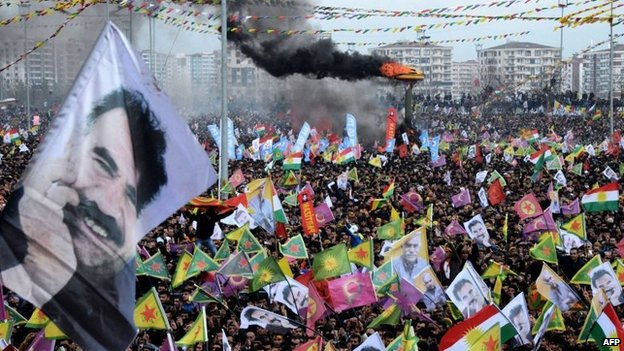 Smoke rises from a fire burning as people wave Kurdish flags and pictures of jailed Kurdish rebel leader Abdullah Ocalan as they gather to celebrate Newroz, the Kurdish New Year, in the south eastern Turkish city of Diyarbakir, 21 March 2015