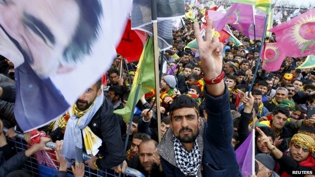 People gesture while others wave Kurdish flags and pictures of Abdullah Ocalan, during a gathering celebrating Newroz in Diyarbakir, Turkey, 21 March 2015