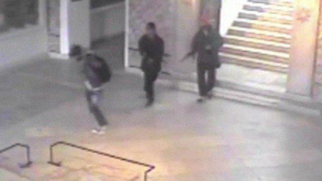 Two gunmen point guns at third man
