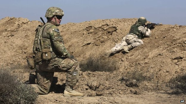 A US soldier trains an Iraqi security forces member in a shooting drill in Taji, north of Baghdad, Iraq, 21 March 2015