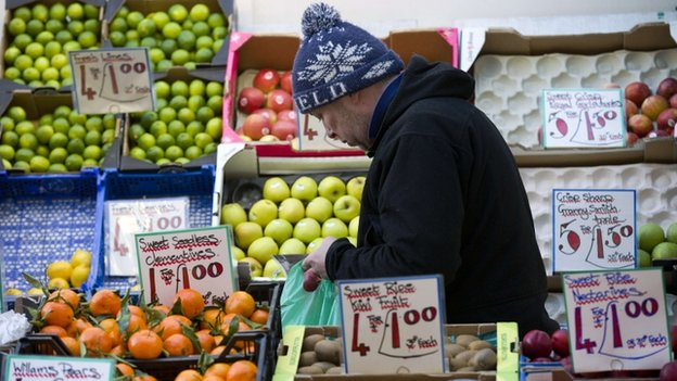 A stall worker bags up fruit for a customer at a market in Soho, central London