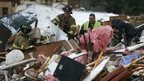 Rescuers work to free a man from a pile of rubble after a round of severe weather hit a mobile home park