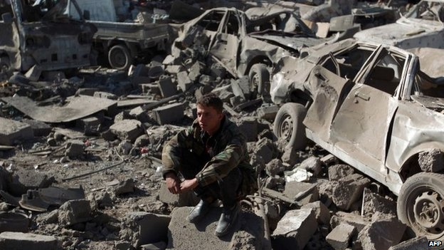 A member of the Yemeni security forces sits near cars destroyed by Saudi-led coalition air strikes in Sanaa (26 March 2015)