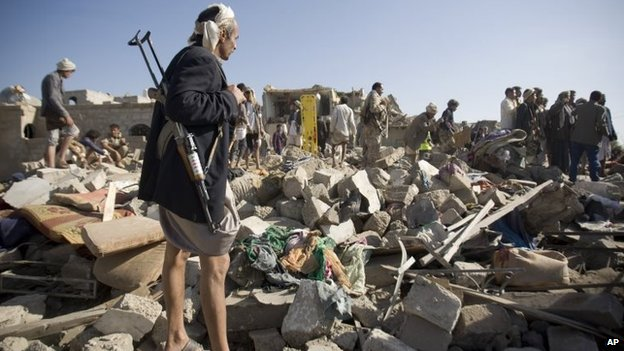 A Houthi fighter stand guard as people search for survivors under the rubble of houses destroyed by Saudi airstrikes near Sanaa airport, Yemen, Thursday, 26 March 2015