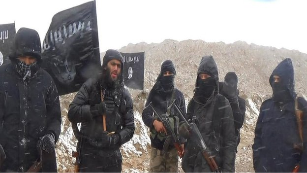 A group of men, mostly masked, standing under an Islamic State flag. Ifthekar Jaman is the only person whose face can be seen