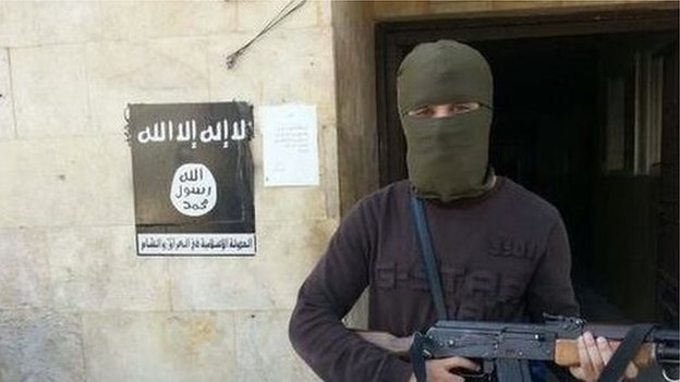 Abu Qa'qa holding a gun, with his face covered
