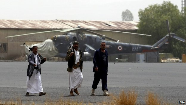 Armed members of Houthi militias walk on the tarmac of the military airport following an alleged airstrike by the Saudi-led coalition in Sana'a, Yemen, 28 March 2015